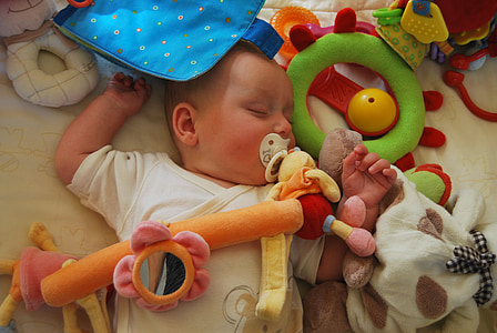 baby sleeping on white fabric sheet surrounded by toys