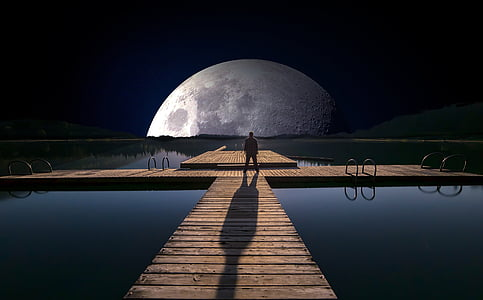 man standing on wooden dock at night