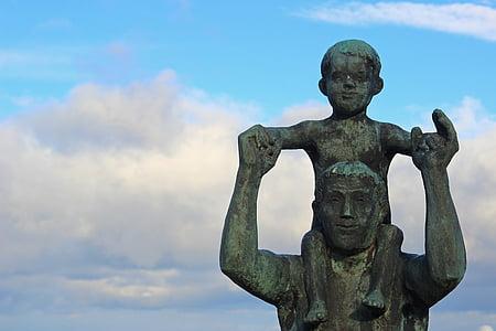 boy on man's shoulder ceramic figurine