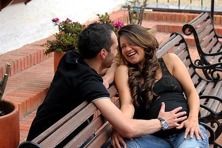 man holding woman sitting on bench during daytime