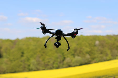 black drone hovering near forest
