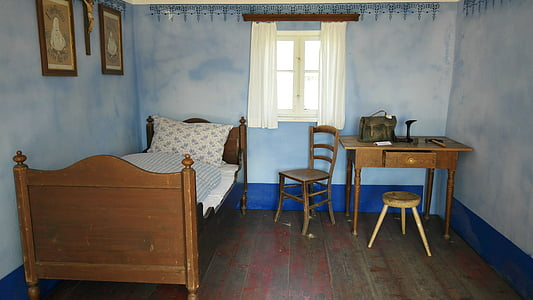 brown wooden bed and white mattress near table and window
