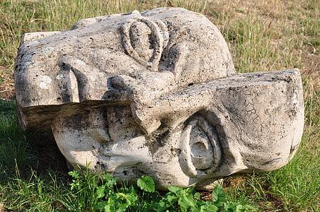 split gray statue head decor on grass