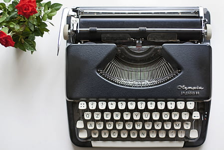 aerial view photography of black typewriter beside red roses