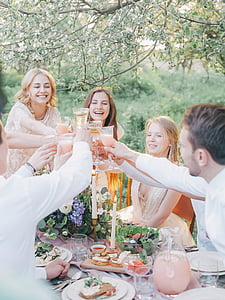 people holding footed glasses in front of dining table