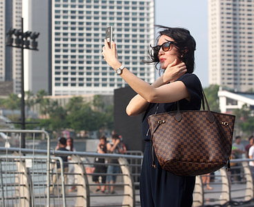 woman wearing tote bag holding silver-colored smartphone