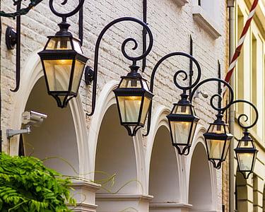 five turned-on black outdoor lanterns