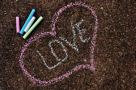 love text inside pink heart beside assorted-color chalks