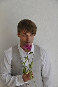 man holding purple flower