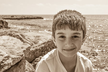sepia photography of boy standing on cliff mountain fronting body of water