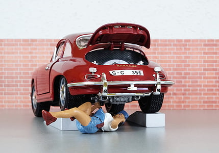 person lying under car while repairing scale model