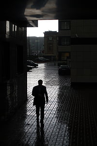 silhouette of man walking inside building