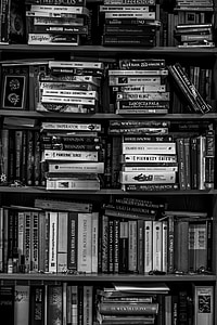 grayscale photo of piled books