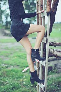 woman wearing black long-sleeved shirt and black skirt on ladder