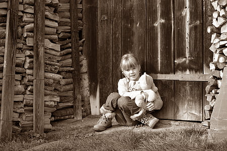 grayscale girl sitting beside brown fence