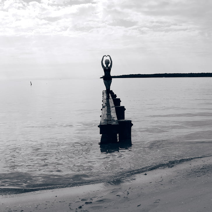 grayscale photo of woman standing on rock formation on sea