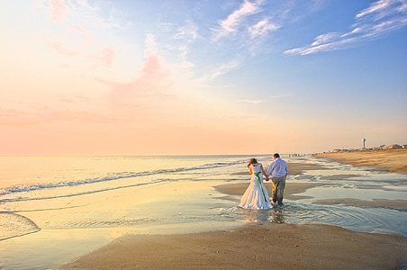 couple holding hands on shore near sea
