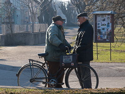 two men talking in front of bicycle on street
