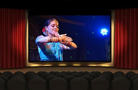 theater showing woman wearing blue dress