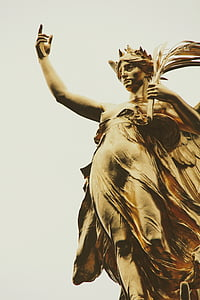 woman raising her right hand while holding branch with leaves on her left hand brass-colored statue low-angle photo