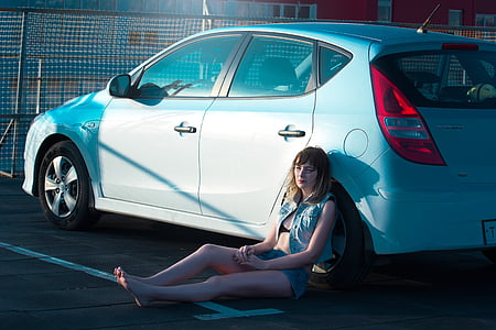 woman wearing blue denim jacket and shorts leaning on white 5-door hatchback