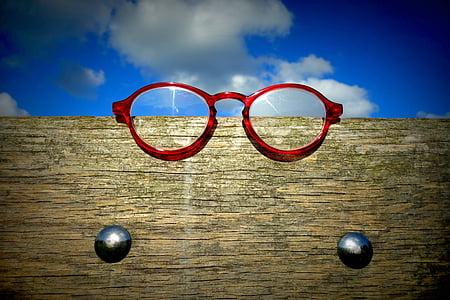 red framed eyeglasses on brown wooden frame
