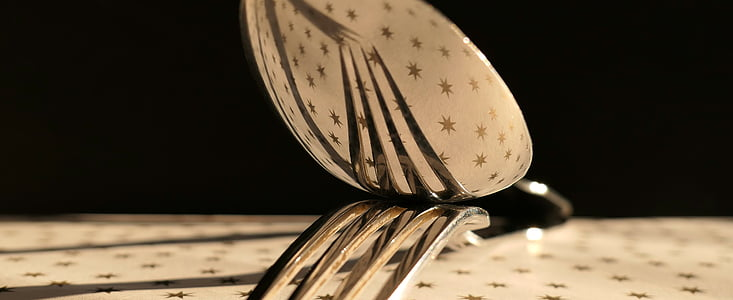 stainless steel spoon top of fork on table