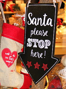 Santa Please Stop Here signage beside christmas stocking