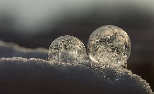 three round ornaments on snow closeup photo