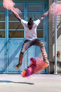 timelapse photo of man jump with skateboard and assorted-color powders at daytime