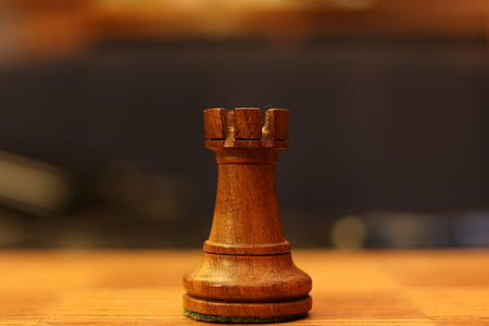 brown chess piece on brown wood