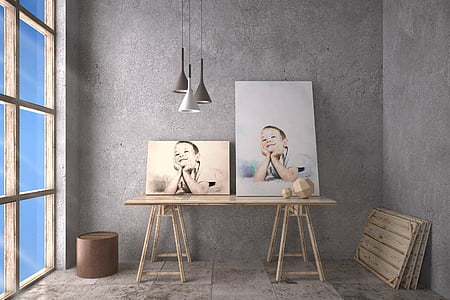 two paintings of boy on top of wooden table