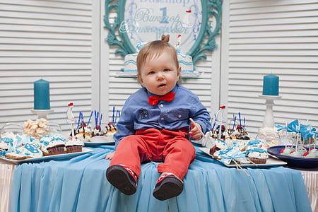 child in blue dress shirt and red pants