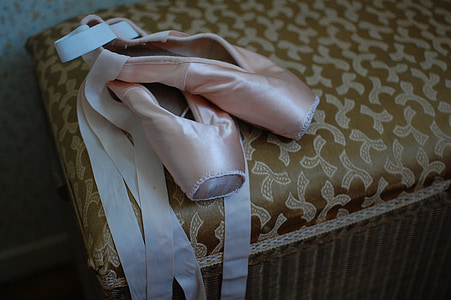 pair of pink ballet shoes on brown fabric ottoman