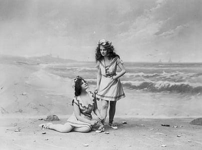 two women wearing dresses near seashore painting