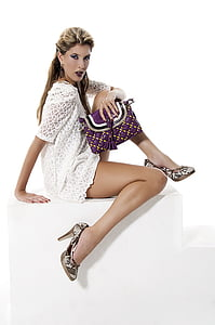 woman in white eyelet shirt dress holding handbag
