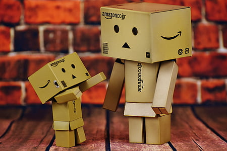 two Amazon box figure on brown wooden board
