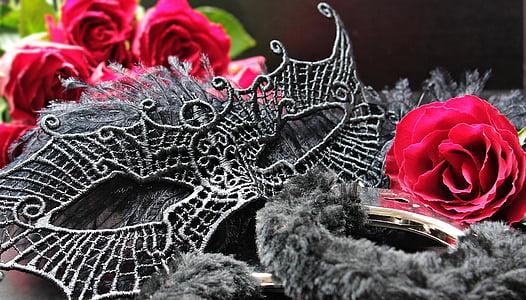 grey mask near red rose flower