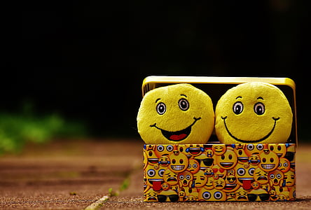 two yellow smile emoji pillows