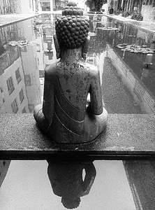 gray scale photography of Gautama Buddha sitting in front pond