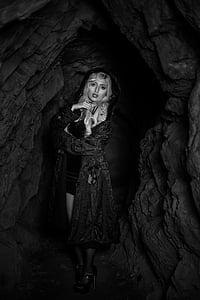 grayscale photography of woman wearing robe inside cave