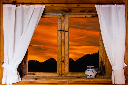 brown wooden window with two curtains and view of orange sunset