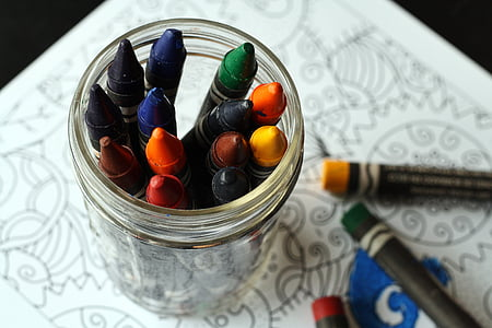 assorted-color crayons in clear glass jar