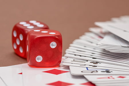 two red dice and playing cards