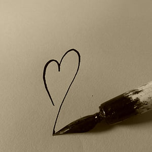 black and white paint brush draws heart on paper
