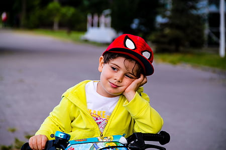 boy wearing yellow zip-up jacket and spiderman cap
