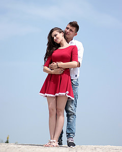 man wearing white long-sleeved shirt and blue denim jeans hugging woman wearing red elbow-sleeved dress standing on gray sand during daytime