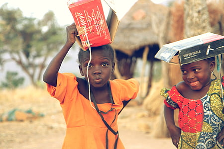 two girl's playing with boxes during daytime