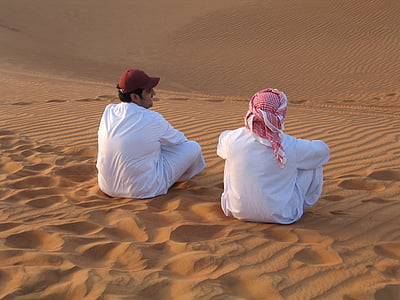 two man sitting on desert