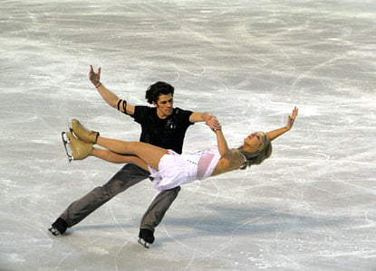 man and woman performing ice skates